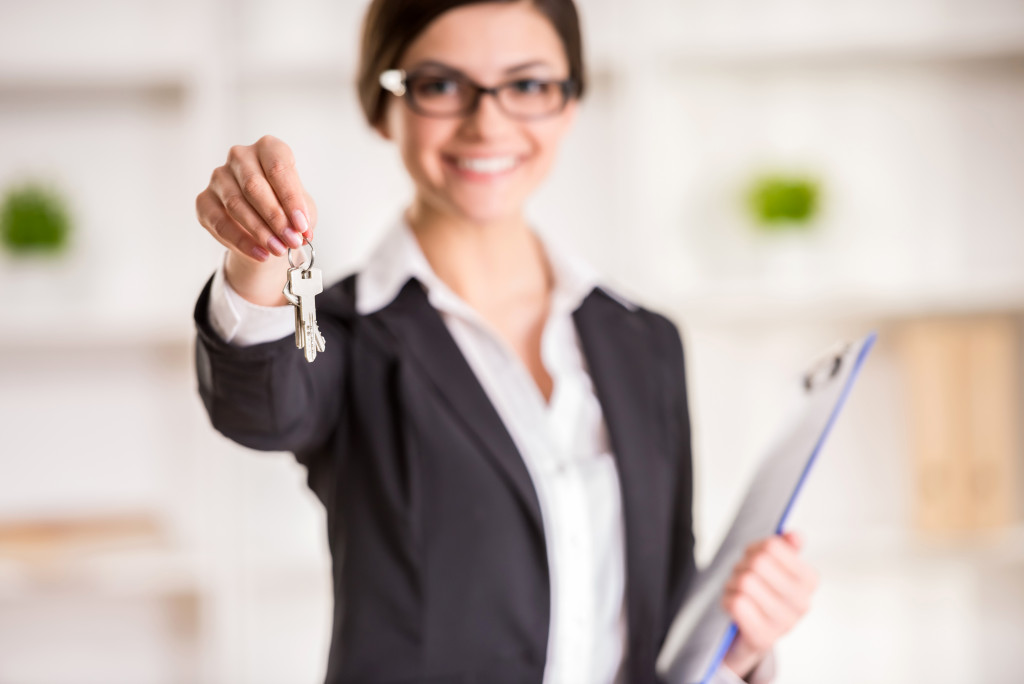 woman holding keys and a clipboard